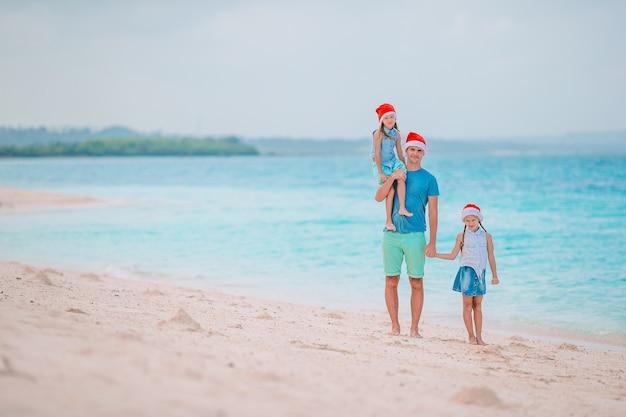 Szczęśliwa rodzina w czerwonych kapeluszach santa na tropikalnej plaży z okazji świąt bożego narodzenia