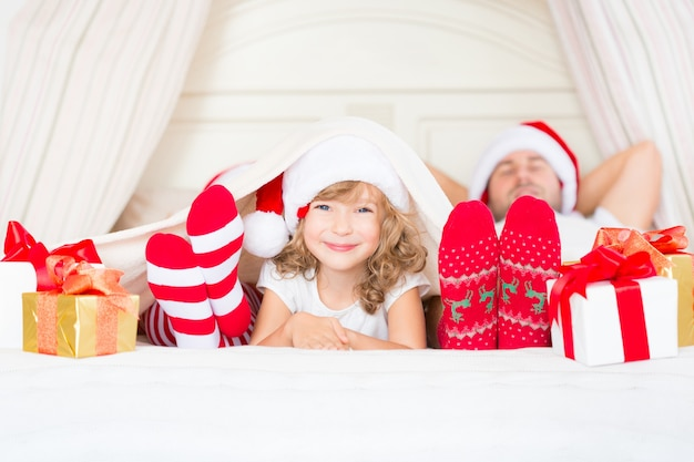 Szczęśliwa rodzina w domu. matka, ojciec i dziecko z prezentem na boże narodzenie. koncepcja ferii zimowych
