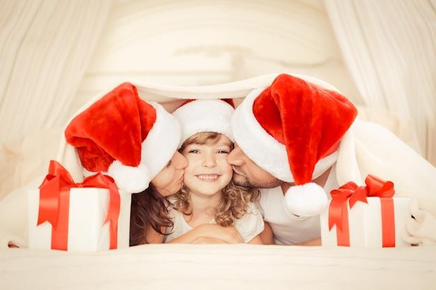 Szczęśliwa rodzina w domu. matka, ojciec i dziecko z prezentem na boże narodzenie. koncepcja świątecznych wakacji