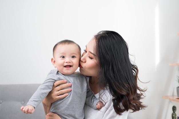 Szczęśliwa rodzina w domu. matka trzyma córkę w salonie w przytulny weekendowy poranek