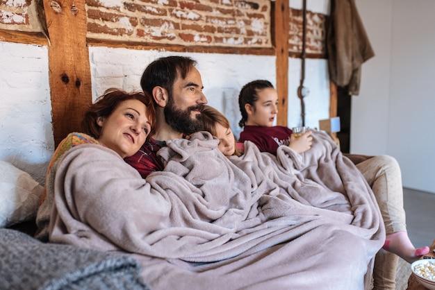 Szczęśliwa rodzina w domu ogląda filmy na kanapie i je popcorn