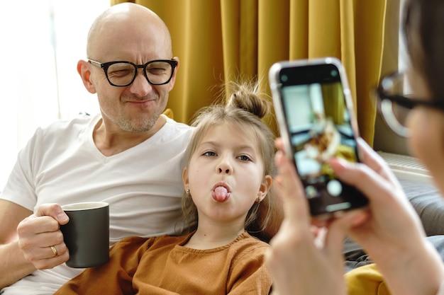 Szczęśliwa rodzina w domu. ojciec i córka pozują dla mamy, która robi zdjęcia smartfonem.