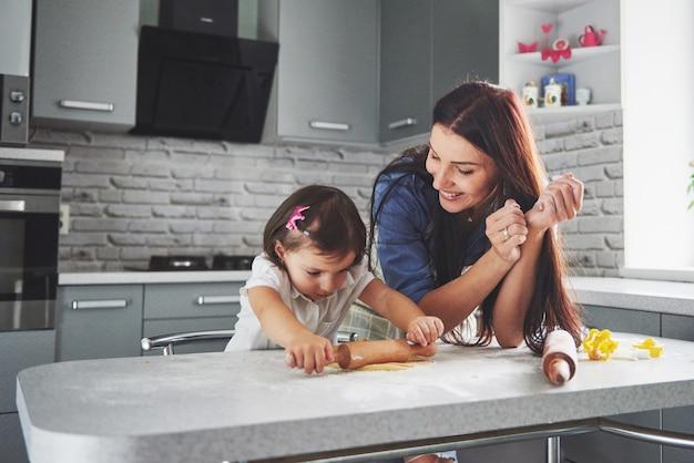 Szczęśliwa rodzina w kuchni. koncepcja żywności na wakacje. matka i córka przygotowują ciasto, piec ciastka. szczęśliwa rodzina w robić ciastkom w domu. domowe jedzenie i mały pomocnik