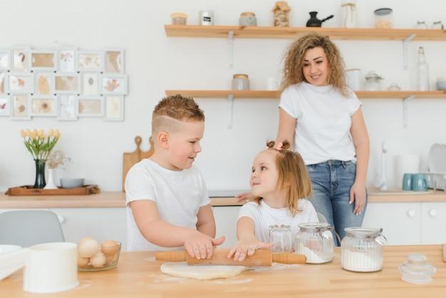 Szczęśliwa rodzina w kuchni. mama i dzieci przygotowują ciasto, pieczą ciasteczka