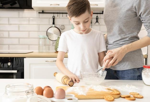 Szczęśliwa rodzina w kuchni. matka i dziecko przygotowanie ciasta, piec ciasteczka