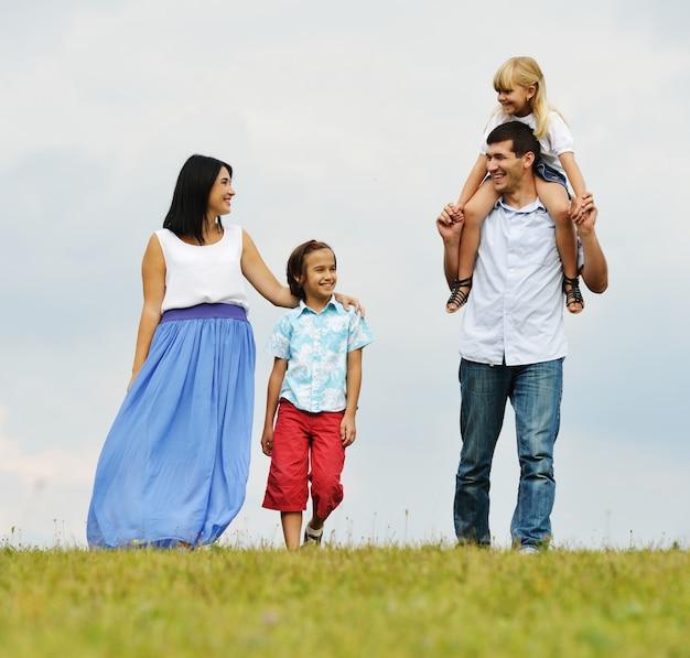 Szczęśliwa rodzina w naturze chodzi na zielonej lato łące