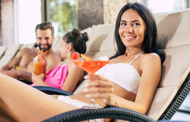 Szczęśliwa rodzina w ośrodku. przystojny ojciec, piękna matka i ich urocza córeczka leżą na leżakach w dużym centrum spa z basenem i piją soki i koktajle