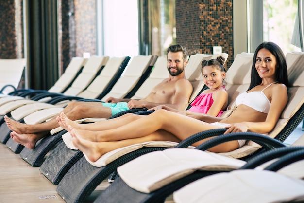 Szczęśliwa rodzina w ośrodku. przystojny ojciec, piękna matka i ich urocza córeczka leżą na leżakach w dużym centrum spa z basenem. relaks na wakacjach