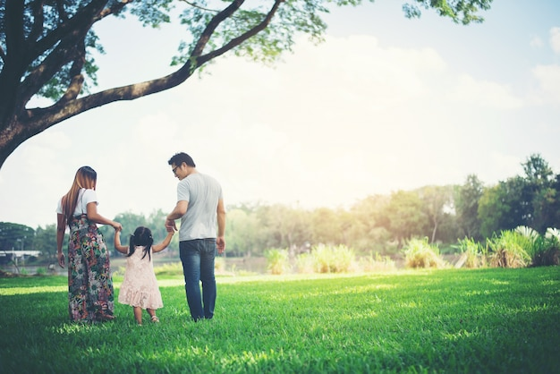 Szczęśliwa rodzina w parku, ojciec i matka bawić się z córką, relaksujemy rodzinnego czas