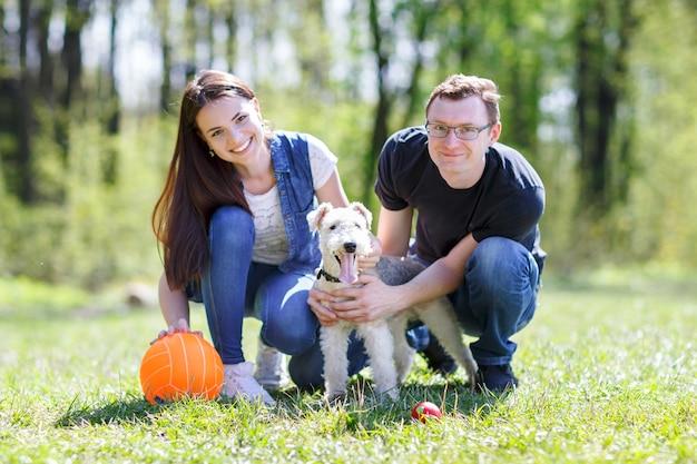 Szczęśliwa rodzina w parku z psem bawić się piłką