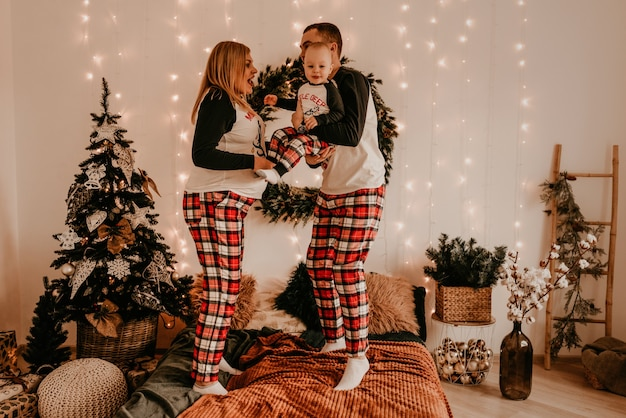Szczęśliwa rodzina w piżamie z rodzicami bawić się z dzieckiem skaczącym na łóżku w sypialni. noworoczne ubrania rodzinne wyglądają stroje. prezenty na walentynki