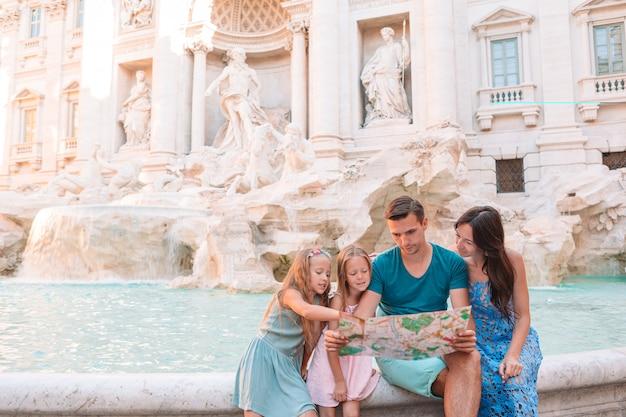 Szczęśliwa rodzina w pobliżu fontany di trevi z mapą miasta
