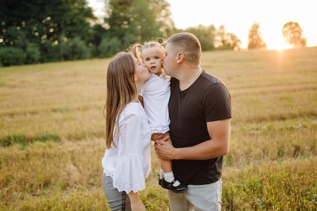 Szczęśliwa rodzina w polu jesienią. matka, ojciec i dziecko bawią się na łonie natury w promieniach zachodzącego słońca