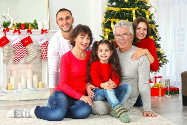 Szczęśliwa rodzina w salonie udekorowanym na boże narodzenie