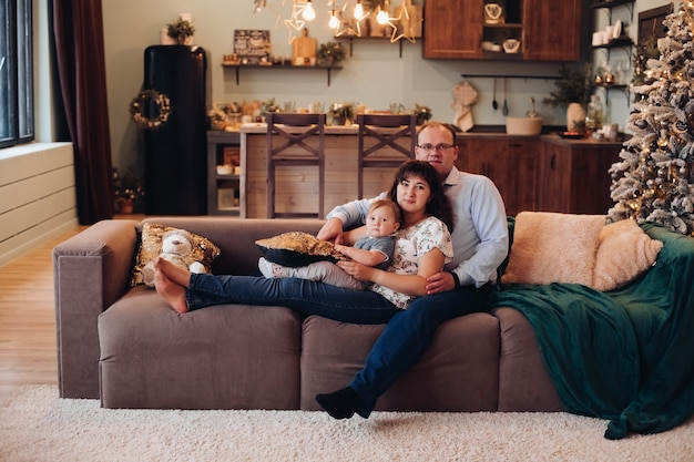 Szczęśliwa rodzina w salonie urządzonym na boże narodzenie.