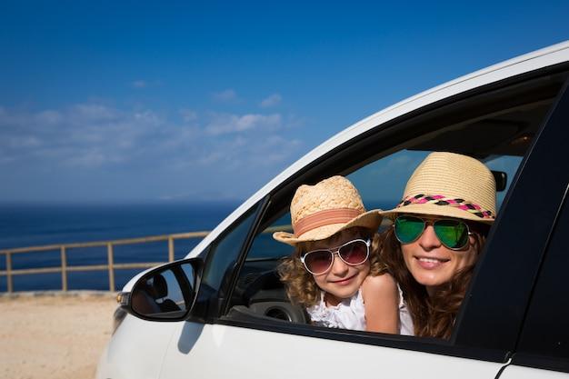 Szczęśliwa rodzina w samochodzie na tle morza i nieba letnie wakacje