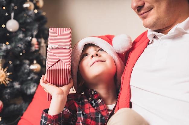 Szczęśliwa rodzina w santa hat, ojciec i syn dziecko daje prezent na boże narodzenie w domu