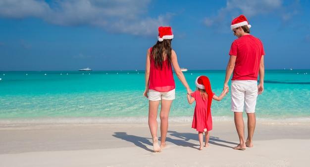 Szczęśliwa rodzina w santa kapelusze ma zabawę podczas karaibskich wakacji