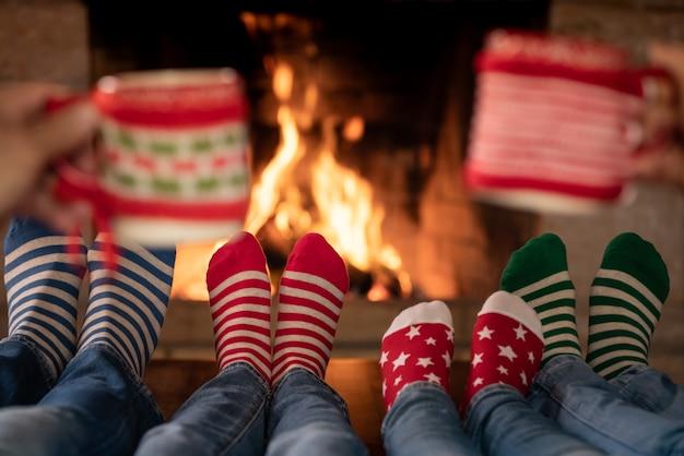 Szczęśliwa rodzina w świątecznych skarpetkach przy kominku matka tata i dzieci w okresie bożego narodzenia