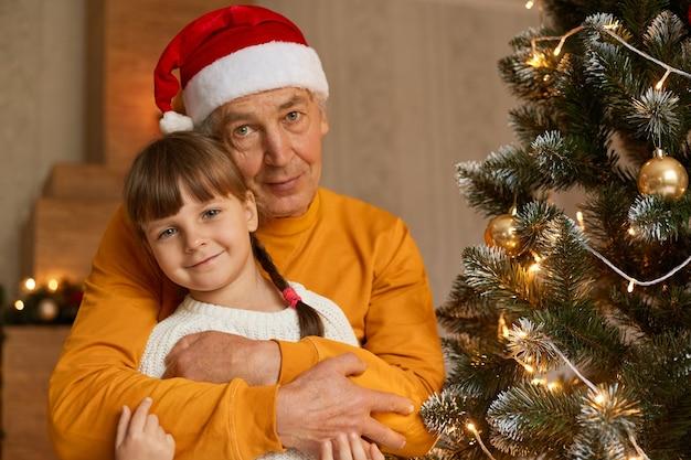 Szczęśliwa rodzina w wigilię bożego narodzenia, starszy mężczyzna przytulanie uroczej dziewczynki z warkoczykami ubiera białą koszulę