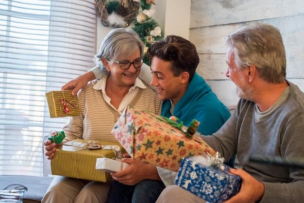 Szczęśliwa rodzina w wigilię bożego narodzenia z dziadkami i wnukiem nastolatka bawiących się z wymianą prezentów w domu na kanapie