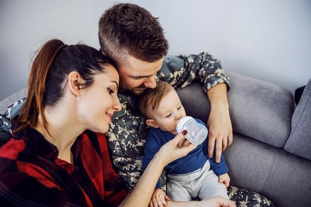 Szczęśliwa rodzina wreszcie jest razem. dzielny żołnierz przyjeżdża do domu i spędza czas z żoną i synem. kobieta trzyma butelkę z wodą. maluch pije.