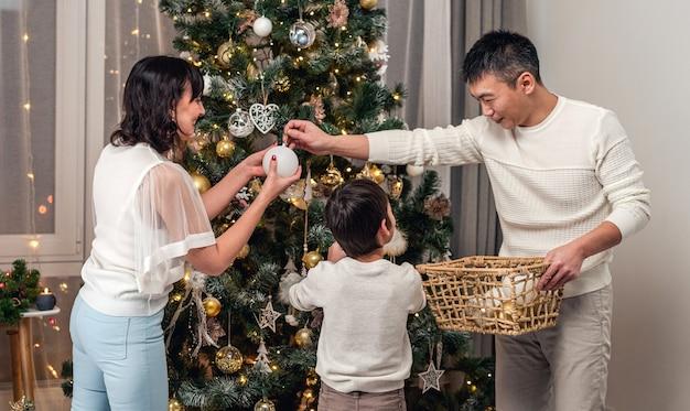 Szczęśliwa rodzina wspólnie dekoruje choinkę przed świętowaniem w domu