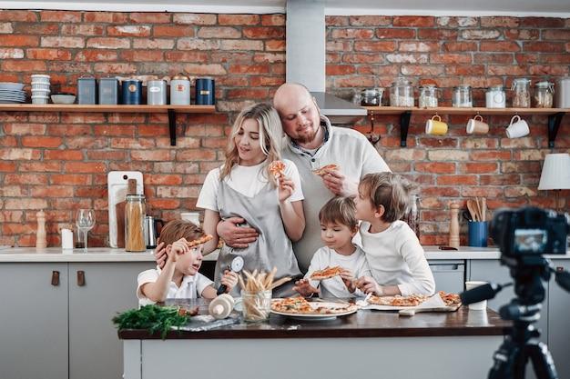 Szczęśliwa rodzina wspólnie gotuje jedzenie i pizzę oraz transmituje swoje sukcesy w telewizji. chłopcy w wieku przedszkolnym i ich rodzice.