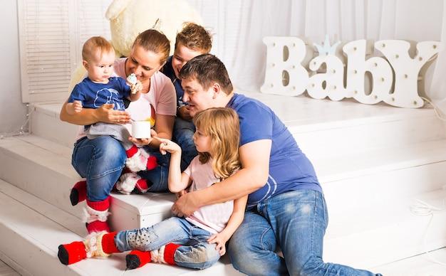 Szczęśliwa rodzina z 3 dziećmi siedzi na podłodze salonu w domu.