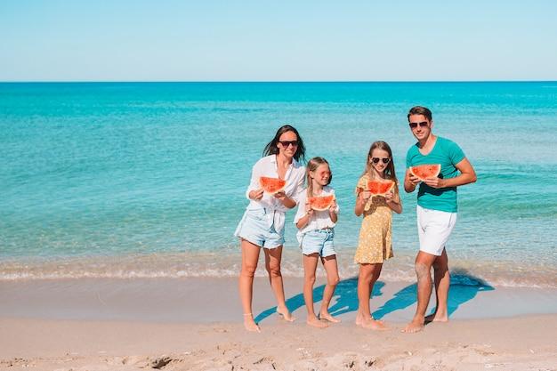 Szczęśliwa rodzina z arbuzem na plaży. rodzice i dzieci bawią się nad morzem.