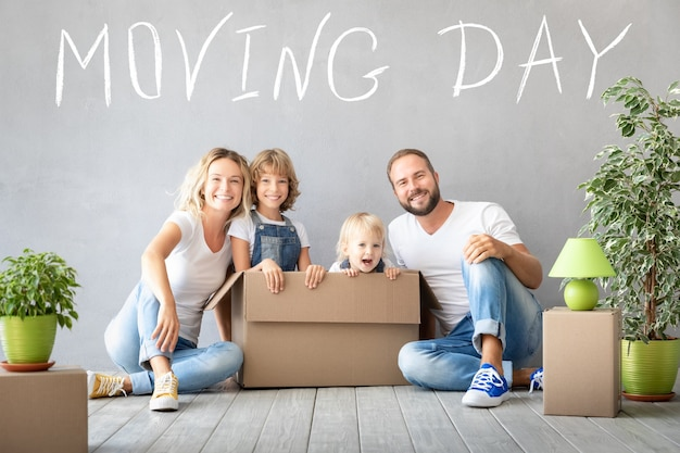 Szczęśliwa rodzina z dwójką dzieci bawiące się w nowym domu