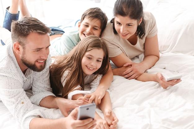 Szczęśliwa rodzina z dwójką dzieci, śmiejąc się i biorąc selfie na smartfonie, leżąc razem na łóżku w mieszkaniu