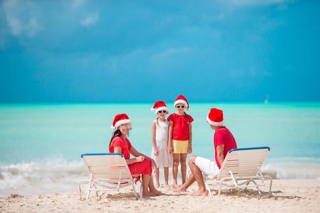Szczęśliwa rodzina z dwójką dzieci w santa hat na wakacje