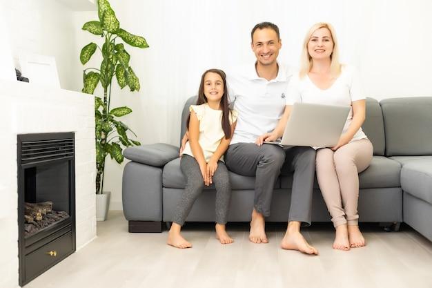 Szczęśliwa rodzina z dzieckiem dziewczyna bawi się razem przy użyciu laptopa siedząc na kanapie, rodzice i córka dziecka, śmiejąc się, relaksując się w domu z komputerem, oglądając śmieszne wideo w internecie, nawiązując połączenie online