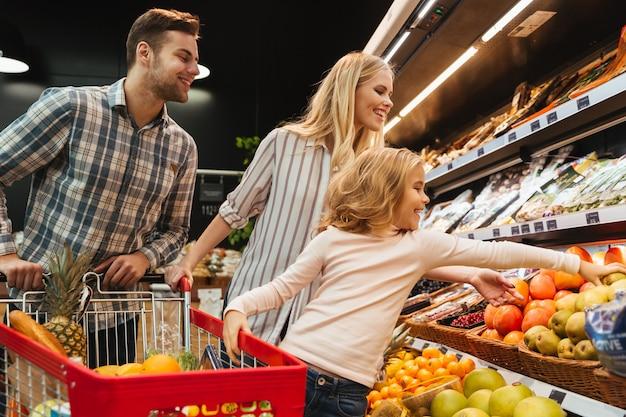 Szczęśliwa rodzina z dzieckiem i wózek na zakupy kupuje jedzenie
