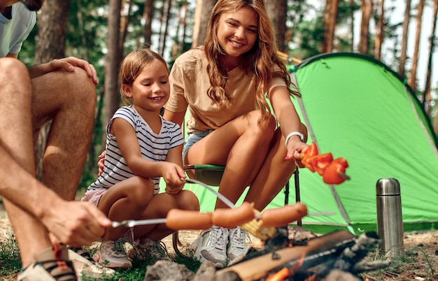 Szczęśliwa rodzina z dzieckiem na pikniku siedzi przy ognisku przy namiocie i grilluje w sosnowym lesie. camping, rekreacja, turystyka.