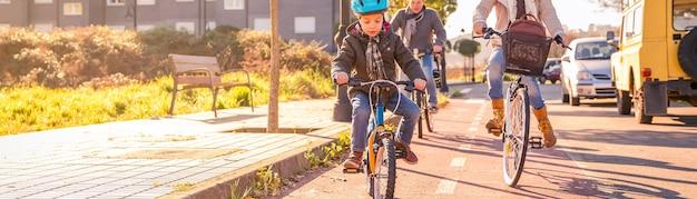 Szczęśliwa rodzina z dzieckiem na rowerach pod miastem w słoneczny zimowy dzień