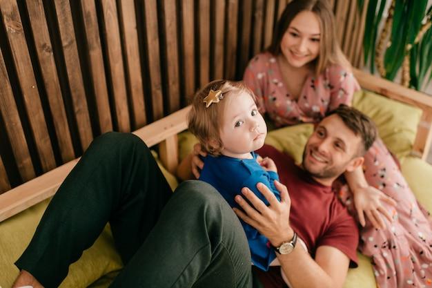 Szczęśliwa rodzina z dzieckiem w łóżku.
