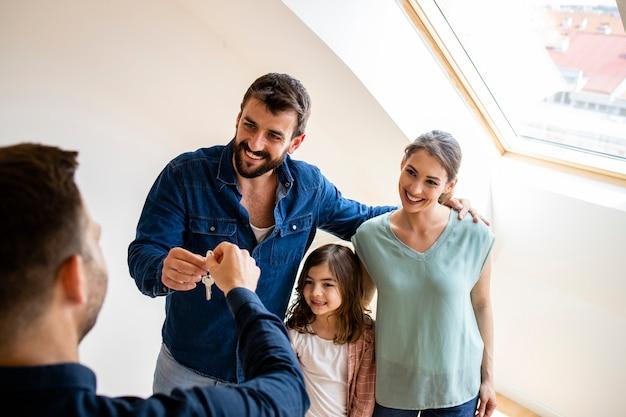 Szczęśliwa rodzina z dziećmi kupując nieruchomość lub odbierając klucze do nowego domu od agenta nieruchomości