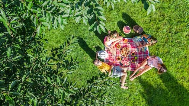 Szczęśliwa rodzina z dziećmi na pikniku w parku rodzice z dziećmi siedzącymi na trawie w ogrodzie