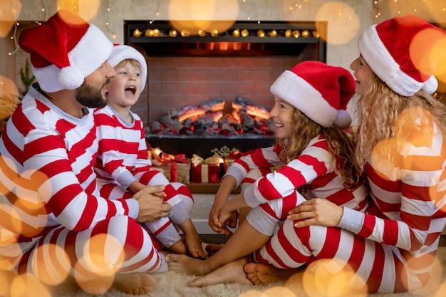 Szczęśliwa rodzina z dziećmi na sobie piżamę w paski przy kominku na boże narodzenie. matka, ojciec i dzieci bawią się w domu.