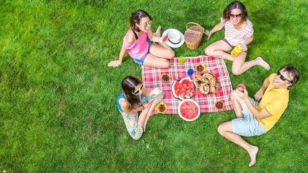 Szczęśliwa rodzina z dziećmi piknik w parku, rodzice z dziećmi siedzą na trawie w ogrodzie i jedzą zdrowe posiłki na świeżym powietrzu