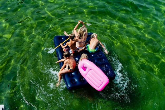 Szczęśliwa rodzina z dziećmi pływa i bawi się w morzu na dmuchanym materacu.