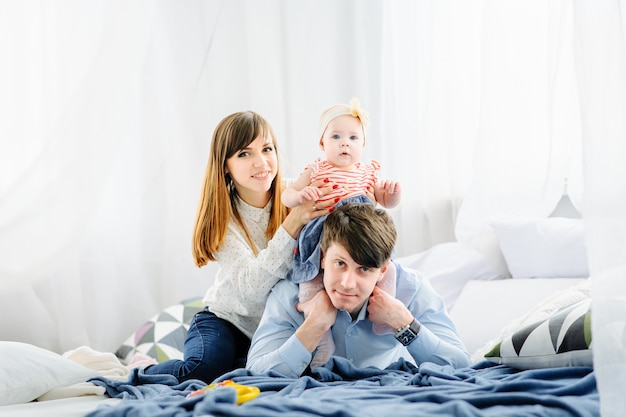 Szczęśliwa rodzina z dziećmi w sypialni