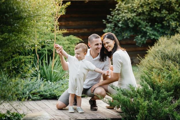 Szczęśliwa rodzina z ich synem spaceru w parku o zachodzie słońca. szczęście. miłość