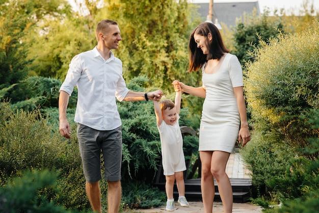 Szczęśliwa rodzina z ich synem spaceru w parku o zachodzie słońca. szczęście. miłość.
