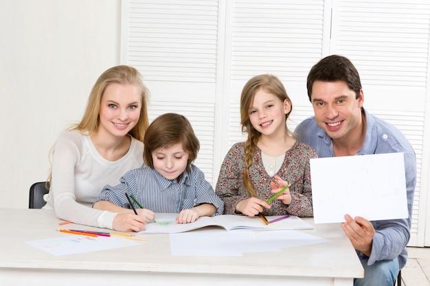 Szczęśliwa rodzina z kolorowymi ołówkami i śmiechem