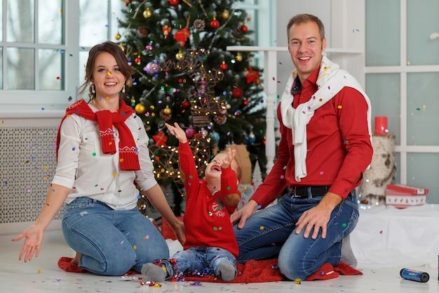 Szczęśliwa rodzina z konfetti na tle choinki z prezentami. święta nowego roku.