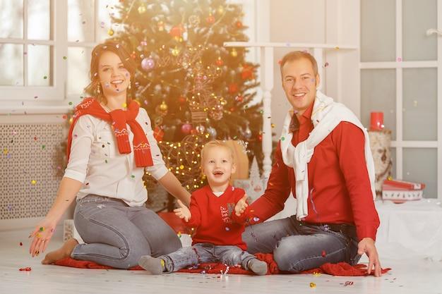 Szczęśliwa rodzina z konfetti na tle choinki z prezentami.