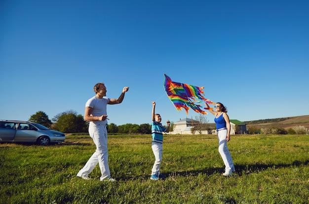 Szczęśliwa rodzina z latawcem grającym w polu w przyrodzie